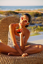 Young Woman in Bathing Suit  Drinking Cocktail