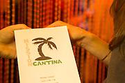 New York, NY - 11 February 2014. A hostess showing a patron the menu at Mission Cantina.