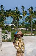 A woman walking with a basket on her head.  Matemwe, Zanzibar, Tanzania