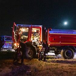 """Suivi durant 24 heures de l'activité de pompiers, en majorité volontaires, du SDIS 13, déployés en GIFF (Groupe d'Intervention Feu de Forêt) pour lutter contre les départs d'incendie. A la fin de cette journée particulièrement calme, le CODIS annonce au GIFF qu'il rejoint une colonne extra-départementale partant des Bouches-du-Rhône. Celle-ci devra prêter main-forte aux sapeurs-pompiers de l'Hérault confrontés à plusieurs départs de feu sur le territoire attisés par des vents soutenus tandis que les moyens aériens nationaux sont limités du fait d'un important feu dans le Var. Sur place, les renforts sont accueillis par le directeur départemental qui les remercie et leur explique qu'il les a engagés pour soulager ses équipes qui ont lutté toute la journée au sol contre les flammes, puisqu'il a choisi de concentrer le peu de moyens aériens dont il disposait sur un autre gros feu de la zone qui, lui, menaçait des habitations. Les pompiers des quatre GIFF envoyés par le 13 récupèrent des plateaux-repas chauds à la cantine mobile du 34 puis vont rejoindre leurs positions pour la nuit où ils procèdent à l'extinction des dernières souches susceptibles de faire repartir le feu puis restent """"en veille active"""" jusqu'au lever du jour. A 6 heures du matin, la mission de renfort est terminée et la colonne prend la direction de Marseille, non sans faire une halte sur une aire d'autoroute pour prendre café et petit-dejeuner en commun. Août 2021 / Bouches-du-Rhône (13) / FRANCE<br /> Voir toutes les photos de ce reportage (89 photos) https://sandrachenugodefroy.photoshelter.com/gallery/2021-08-GIFF-du-SDIS13-Complet/G0000lDeWrBxRkHY/C0000yuz5WpdBLSQ"""