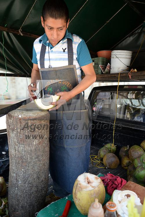 Toluca, México.- La venta de cocos en algunas avenidas del Valle de Toluca es una opción para refrescarse, de forma rápida se ofrece agua o coco con algún condimento para el deleite de los compradores. Agencia MVT / Crisanta Espinosa