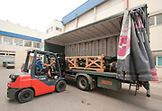 A forklift loads a truck with an irregular pallet of plastic piping