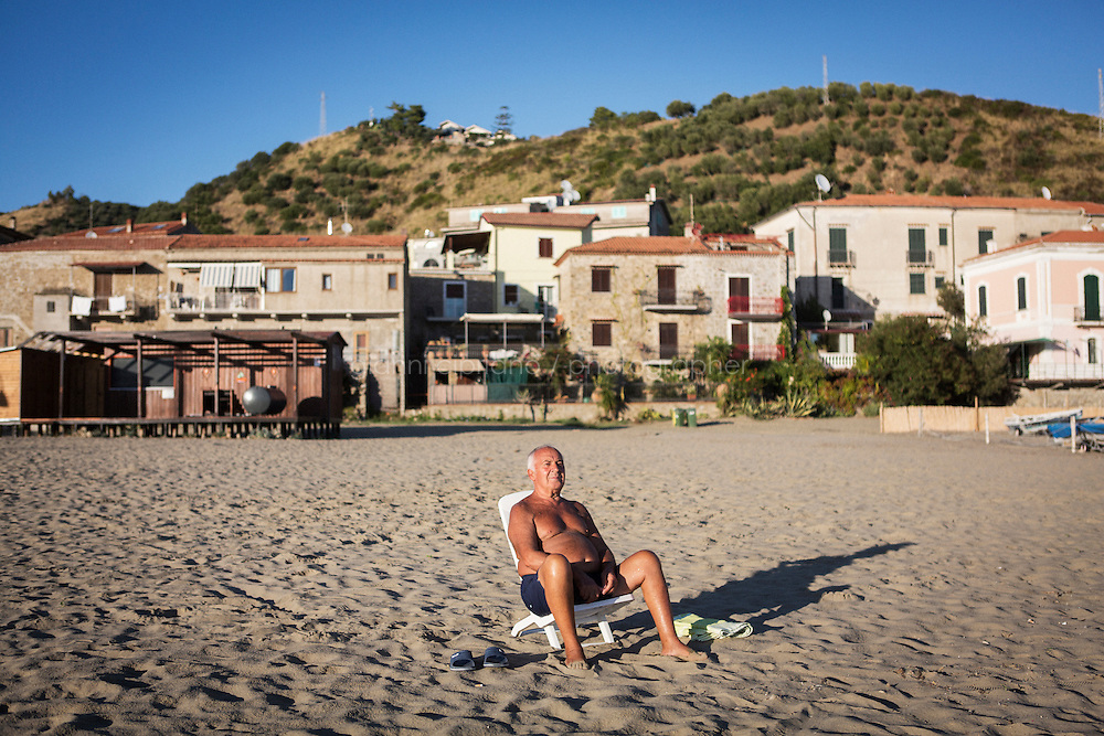 ACCIAROLI (POLLICA), ITALY - 5 OCTOBER 2016: 76-years-old Enzo Speranza relaxes on the beach of Acciaroli, a hamlet in the municipality of Pollica, Italy, on October 5th 2016. Mr Speranza, who lives in Vallo della Lucania (about 30 kilometers from Acciaroli) spends 3 months a year in Acciaroli because of its fresh air and healthy lifestyle. He comes to the beach to exercise and relax every day.<br /> <br /> To understand how people can live longer throughout the world, researchers at University of California, San Diego School of Medicine have teamed up with colleagues at University of Rome La Sapienza to study a group of 300 citizens, all over 100 years old, living in Acciaroli (Pollica), a remote Italian village nestled between the ocean and mountains in Cilento, southern Italy.<br /> <br /> About 1-in-60 of the area's inhabitants are older than 90, according to the researchers. Such a concentration rivals that of other so-called blue zones, like Sardinia and Okinawa, which have unusually large percentages of very old people. In the 2010 census, about 1-in-163 Americans were 90 or older.
