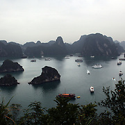 The view of tourist junks and surrounding islands from the vantage point of Titop Island, Ha Long Bay, Vietnam. The bay consists of a dense cluster of 1,969 limestone monolithic islands. Ha Long Bay, is a UNESCO World Heritage Site, and a popular tourist destination. Ha Long, Bay, Vietnam. 11th March 2012. Photo Tim Clayton