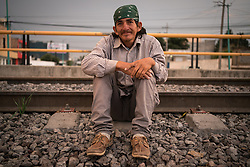 A Honduran migrant, name withheld, sits on the rail tracks as he waits for the train known as La Bestia.
