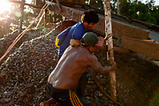 Two miners reinforce the knots of the logs that support the ramp where the mud slides and the gold particles get trapped in carpets in the peruvian Amazon.