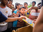 """07 AUGUST 2014 - BANGKOK, THAILAND:  Children line up for free toys during a food distribution at Pek Leng Keng Mangkorn Khiew Shrine in Bangkok. Thousands of people lined up for food distribution at the Pek Leng Keng Mangkorn Khiew Shrine in the Khlong Toei section of Bangkok Thursday. Khlong Toei is one of the poorest sections of Bangkok. The seventh month of the Chinese Lunar calendar is called """"Ghost Month"""" during which ghosts and spirits, including those of the deceased ancestors, come out from the lower realm. It is common for Chinese people to make merit during the month by burning """"hell money"""" and presenting food to the ghosts. At Chinese temples in Thailand, it is also customary to give food to the poorer people in the community.<br />      PHOTO BY JACK KURTZ"""