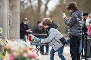 Two young members of the public lay flowers In memory of Prince Philip The Royal Highness the Duke of Edinburgh, London on 9 April 2021.