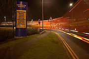 Lights from industrial night traffic speeding through the DIRFT warehouse logistics park in Daventry,