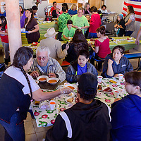 Guests and volunteers share a traditional Thanksgiving meal during the Immanuel Baptist Church Thanksgiving dinner at the Community Outreach Center in Grants Saturday.