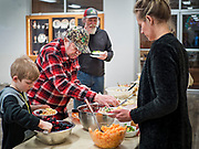 "26 FEBRUARY 2020 - FARMINGTON, MINNESOTA: NICHOLAS FRIEDGES gets a salad at the community dinner at Faith Church, a United Methodist Church in Farmington, MN, about 30 minutes south of the Twin Cities. The dinner is sponsored by Loaves & Fishes, a Christian organization that provides food for community dinners and foodbanks. Farmington, with a population of 21,000, is a farming community that has become a Twin Cities suburb. The city lost its only grocery store, a Family Fresh Market, in December, 2019. The closing turned the town into a ""food desert."" In January, Faith Church started serving the weekly meals as a response to the store's closing. About 125 people per week attend the meal at the church, which is just a few blocks from the closed grocery store. The USDA defines food deserts as having at least 33% or 500 people of a census tract's population in an urban area living 1 mile from a large grocery store or supermarket. Grocery chains Hy-Vee and Aldi both own land in Farmington but they have not said when they plan to build or open stores in the town.       PHOTO BY JACK KURTZ"
