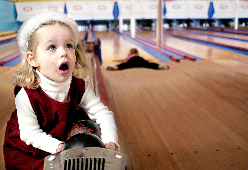 Sara Heubeck, age 3, left, grabs one of the tiny duckpin bowing balls before methodically droping it onto the alley. Reveling in the means, she fails to pay attention to the ends, resulting in 5 or 6 stalled bowling balls mid-lane. Her sister Viviann, right, performs a graceful split in her socks while launching a bowling ball. Community members from the Thornleigh neighborhood gathered at Taylor's Stonleigh Duckpin Bowling Center, located on York Rd., Friday night, from 7-10PM, January 28, 2005, for their 5th annual neighborhood bowling party.