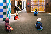 17 FEBRUARY 2021 - DES MOINES, IOWA: Pre-kindergarten students sitting socially distanced and wearing face masks wait to register at Walnut Street School in downtown Des Moines. Des Moines Public Schools (DMPS) opened to in person education this week after teaching most of the 2020-2021 school year either remotely or with a hybrid/remote learning model. The district has ended its hybrid model. The Governor of Iowa has aggressively pushed schools to return to in person education, going so far as to threaten to withhold funds from districts that don't return to in person classes. DMPS, the largest school district in Iowa, has resisted the Governor's push because Polk County, IA, has been a Coronavirus/COVID-19 hotspot with positivity rates well above 10 percent. The district was recently able to vaccinate many teachers and positivity rates have fallen to 9 percent, making it safer to reopen schools.        PHOTO BY JACK KURTZ