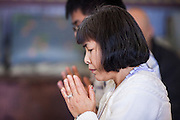 """11 MARCH 2012 - CHANDLER, AZ:     People participate in Buddhist chanting in the """"bot"""" or ordination hall during Makha Bucha Day services at Wat Pa in Chandler, AZ, Sunday. Magha Puja (also spelled Makha Bucha) Day marks the day 2,500 years ago that 1,250 Sangha came spontaneously to see the Buddha who preached to them on the full moon. All of them were """"Arhantas"""" or Enlightened Ones who had been personally ordained by the Buddha. The Buddha gave them the principles of Buddhism, called """"The Ovadhapatimokha."""" Those principles are: to cease from all evil, to do what is good, and to cleanse one's mind. It is one of the most important holy days in the Theravada Buddhist tradition. At the temple, people participate in the """"Tum Boon"""" (making merit by listening to the monk's preaching and giving a donation to the temple), the """"Rub Sil"""" (keeping of the Five Precepts including the abstinence from alcohol and other immoral acts) and the """"Tuk Bard"""" (offering food to the monks in their alms bowls). It is a day for veneration of the Buddha and his teachings. It's a legal holiday in Thailand, Laos, Cambodia and Myanmar (Burma).     PHOTO BY JACK KURTZ"""