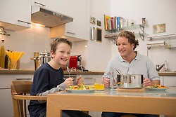 Father and son eating in kitchen
