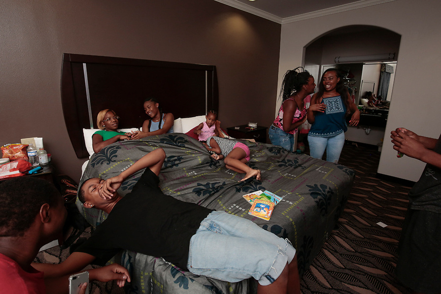 """Coby Cochran, (L) and her daughters Elizabeth Thomas, 2, center, and Melanie Thomas, 7, receive a visit in their FEMA provided hotel room from family members in the aftermath of tropical storm Harvey in Houston, Texas, U.S. September 10, 2017. """"I'm a single mom and it's hard losing everything, but God is going to take care of us no matter what. Just live and love,"""" said Cochran.  """"Momma I'm happy as long as we're together,"""" said Melanie Thomas."""