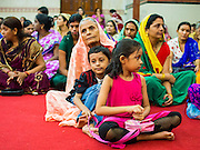 17 AUGUST 2014 - BANGKOK, THAILAND:     A woman with her grandchildren during Krishna Janmashtami services at the Vishnu temple in Bangkok. Krishna Janmashtami is the annual celebration of the birth of the Hindu deity Krishna, the eighth avatar of the Hindu god Vishnu. It is celebrated by Hindus in Thailand. There are about 53,000 Hindus in Thailand, most originally from India, but many Hindu deities are highly revered by Thai Buddhists and Hindu holy days are observed by many Thai Buddhists.  PHOTO BY JACK KURTZ