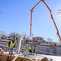 010814       Cable Hoover<br /> <br /> A giant pump crane hovers over the work site as workers from construction contractor Noel Company smooth the slab of concrete that will form the parking garage of the Hooghan Hozho housing project in downtown Gallup Wednesday.