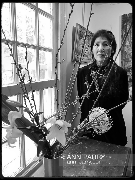 Manhasset, New York, U.S., April 8, 2018. Artist poses behind her flower arrangement in vase at Reception for The Art Guild exhibition is held at Elderfields Preserve.