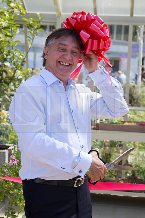© Licensed to London News Pictures. 19/05/2014. London, England. Michelin Star Chef Raymond Blanc cuts a ribbon at the Hartley Botanic Ltd tradestand.  Press Day at the RHS Chelsea Flower Show. On Tuesday, 20 May 2014 the flower show will open its doors to the public.  Photo credit: Bettina Strenske/LNP