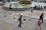 A man holds a child upside-down over waters of the fountains in Trafalgar Square, on 13th August 2018, in London, England.