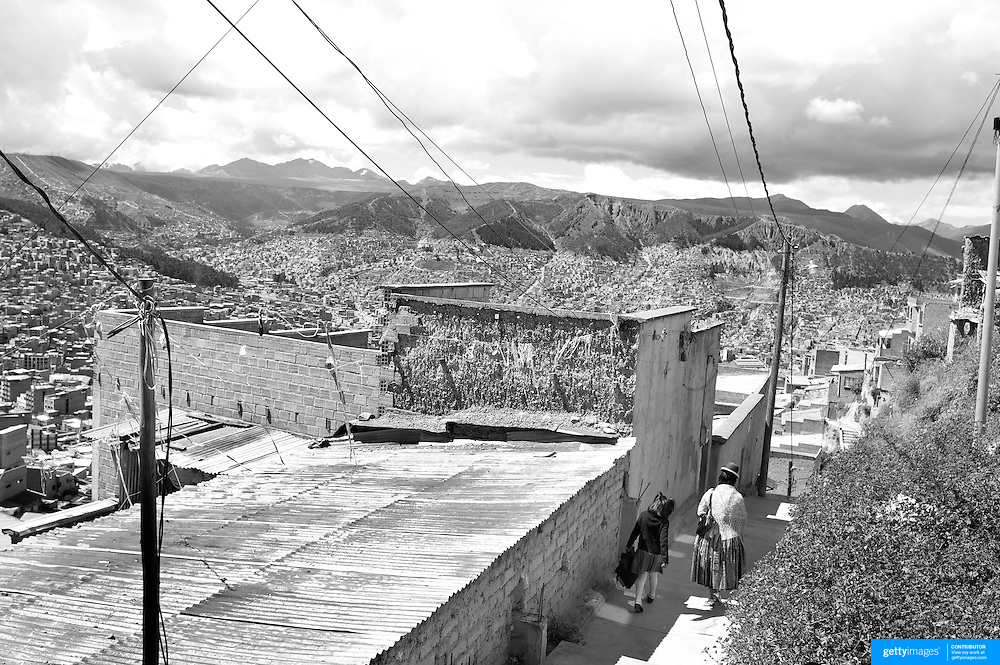 Cholita wrestler Yolanda La Amorosa arrives at her home (left) on the hillside of La Paz with her daughter after collecting her from school in La Paz, Bolivia. Yolanda is part of the 'Titans of the Ring' wrestling group who perform every  Sunday at El Alto's Multifunctional Centre. Bolivia. The wrestling group includes the fighting Cholitas, a group of Indigenous Female Lucha Libra wrestlers who fight the men as well as each other for just a few dollars appearance money. El Alto, Bolivia, 17th March 2010. Photo Tim Clayton
