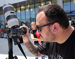 Jose Botero captures the partial eclipse of the sun on his camera from the bottom deck of the Frost Museum in downtown Miami, Fla. Photo by C.M. Guerrero/Miami Herald/TNS/ABACAPRESS.COM