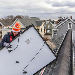Revision Energy employee Skizz Mancini installing solar panels on a multi-family home in Lowell, Massachuetts.