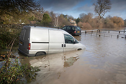 © Licensed to London News Pictures. 21/12/2019. Pulborough, UK. Abandoned vehicles lie half submerged in a car park next to the The River Arun which has burst its banks and flooded local businesses in Pulborough, West Sussex. River levels remain high after heavy overnight rain in the south where more rain is expected today. Photo credit: Peter Macdiarmid/LNP