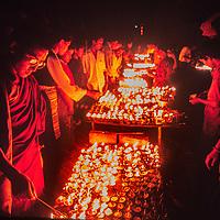 Tibetan Buddhists light votive candles outside Bodh'nath Stup near Kathmandu, Nepal, 1996.