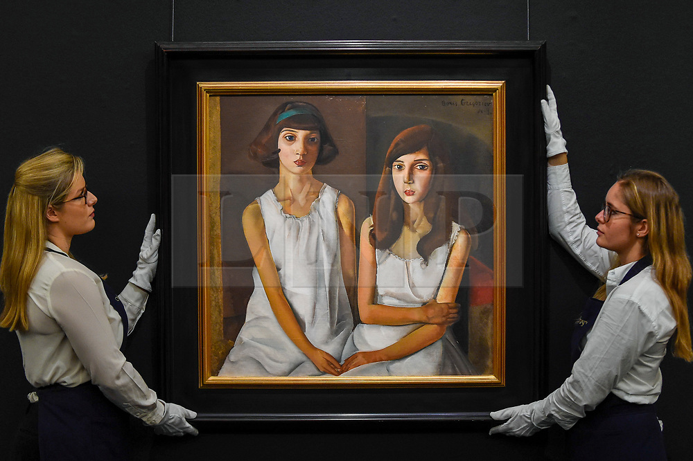 """© Licensed to London News Pictures. 22/11/2019. LONDON, UK. Technicians present """"Les Enfants"""", 1923, by Boris Grigoriev (Est. GBP300-500k) at the preview for the upcoming sales of Russian artworks at Sotheby's New Bond Street.  The Russian Pictures and Works of Art, Fabergé and Icons sales take place on 26 November.  Photo credit: Stephen Chung/LNP"""