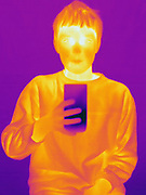 Thermogram of a boy drinking cold water.  This image is part of a series.  The different colors represent different temperatures on the object. The lightest colors are the hottest temperatures, while the darker colors represent a cooler temperature.  Thermography uses special cameras that can detect light in the far-infrared range of the electromagnetic spectrum (900?14,000 nanometers or 0.9?14 µm) and creates an  image of the objects temperature..
