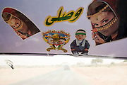 Driving through the Abo Shouk refugee camp, sun visor images of fair-skinned child and lady, are displayed on the windscreen of a vehicle belonging to the Govenor of north Darfur, Sudan.