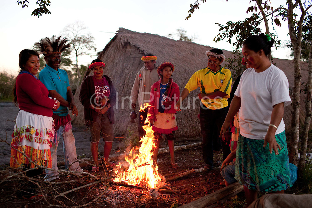 Guarani community male and female standing around a fire at dusk. The Guarani are one of the most populous indigenous populations in Brazil, but with the least amount of land. They mostly live in the State of Mato Grosso do Sul and Mato Grosso. Their tradtional way of life and ancestral land is increasingly at risk from large scale agribusiness and agriculture. There have been recorded cases and allegations of violence between owners of large farms and the Guarani communities in this region.