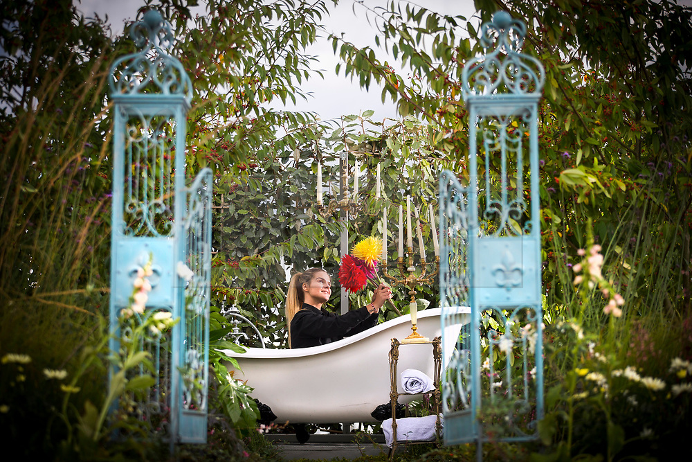 © Licensed to London News Pictures. 14/09/2017. Harrogate UK. Demi Lambe sits in the bathtub in the North of England Horticultural Society show garden that has been designed to be the garden's idyll on staging day at the Autumn Harrogate Flower show that starts tomorrow at the Great Yorkshire show ground. Photo credit: Andrew McCaren/LNP