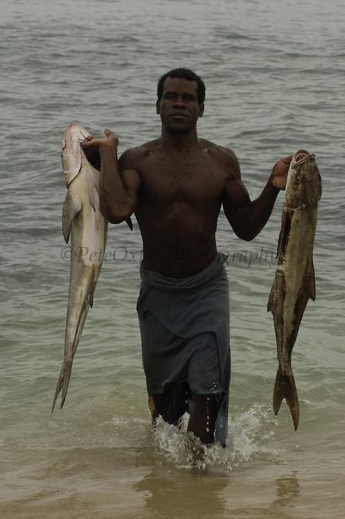 Vezo fisherman bringing catch ashore. Lavanono (Antandroy area) fishing village, south coast of MADAGASCAR