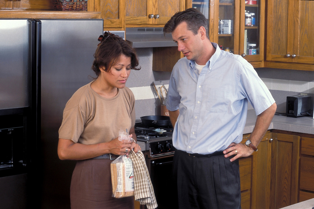 Hispanic woman and Anglo man argue heatedly in kitchen regarding household issues.<br /> ©Bob Daemmrich/