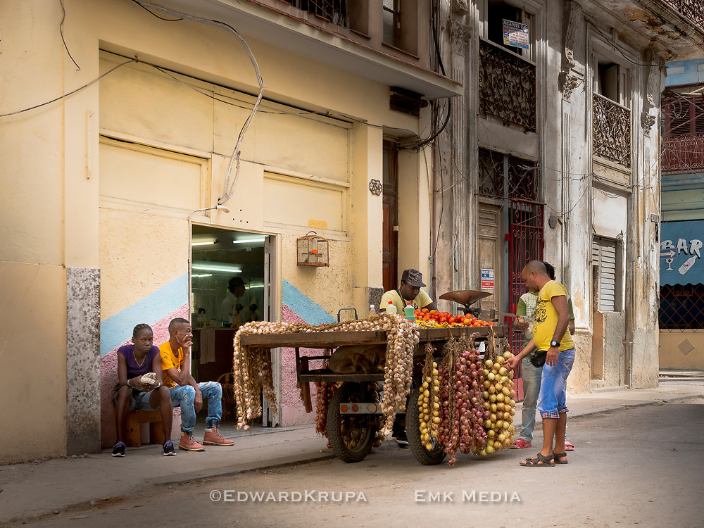 People around a vegetable cart, parked in front of a barber shop, in Havana.