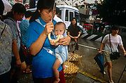 A Macanaese (Portuguese-Chinese) mother carries her baby in a sling on her chest while shopping for supplies in a Macau market, China in this ex-Portuguese colony. Amid a crowded morning market, the shopping is done for families and the elderly during the rainy season.  Macau is now administered by China as a Special Economic Region (SER) and is home to a population of mainland 95% Chinese, primarily Cantonese, Fujianese as well as some Hakka, Shanghainese and overseas Chinese immigrants from Southeast Asia and elsewhere. The remainder are of Portuguese or mixed Chinese-Portuguese ancestry, the so-called Macanese, as well as several thousand Filipino and Thai nationals. The official languages are Portuguese and Chinese.