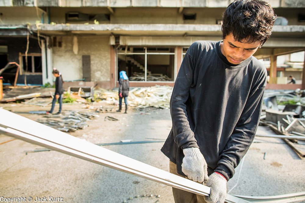 """11 DECEMBER 2012 - BANGKOK, THAILAND:  A worker recycles a door frame from a business in """"Washington Square"""" a notorious entertainment district off Sukhumvit Soi 22 in Bangkok. Demolition workers on many projects in Thailand live on their job site tearing down the building and recycling what can recycled as they do so until the site is no longer inhabitable. They sleep on the floors in the buildings or sometimes in tents, cooking on gas or charcoal stoves working from morning till dark. Sometimes families live and work together, other times just men. Washington Square was one of Bangkok's oldest red light districts. It was closed early 2012 and is being torn down to make way for redevelopment.    PHOTO BY JACK KURTZ"""