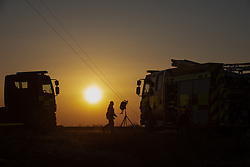 © Licensed to London News Pictures . 27/03/2020. Bolton, UK. Fire-fighters have worked to contain a large fire, reported to have been started by a barbecue, spread across Winter Hill, as people are told to stay at home during the covid 19 coronavirus outbreak . Photo credit: Joel Goodman/LNP