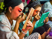 08 DECEMBER 2016 - BANGKOK, THAILAND:  Cast members, one using a mirror with a photo of Bhumibol Adulyadej, the Late King of Thailand, on it put on their makeup before a Chinese opera (also called ngiew in Thailand) performance at Pek Leng Keng Shrine in the Khlong Toei neighborhood of Bangkok. Public performances of music and celebration were banned during the first 30 days of the mourning period for Bhumibol Adulyadej, the Late King of Thailand. Now, nearly two months after the revered monarch's death, Bangkok street life is returning to normal and Chinese temples and shrines are once again scheduling operas.     PHOTO BY JACK KURTZ