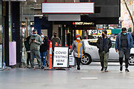 People line up outside a COVID-19 testing Clinic on Bourke Street this afternoon in Melbourne after lockdown was extended for another 7 days on the day it enters 6th day of the state wide COVID-19 lockdown that has been placed on the State of Victoria. (Photo by Michael Currie/Speed Media)