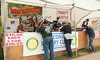 Keith and Lilo Hall man the Laconia Rotary Booth on Lakeside Avenue as folks stop to purchase their chance to win the Harley Davidson Heritage Softtail Classic which will drawn on Sunday.  (Karen Bobotas/for the Laconia Daily Sun)