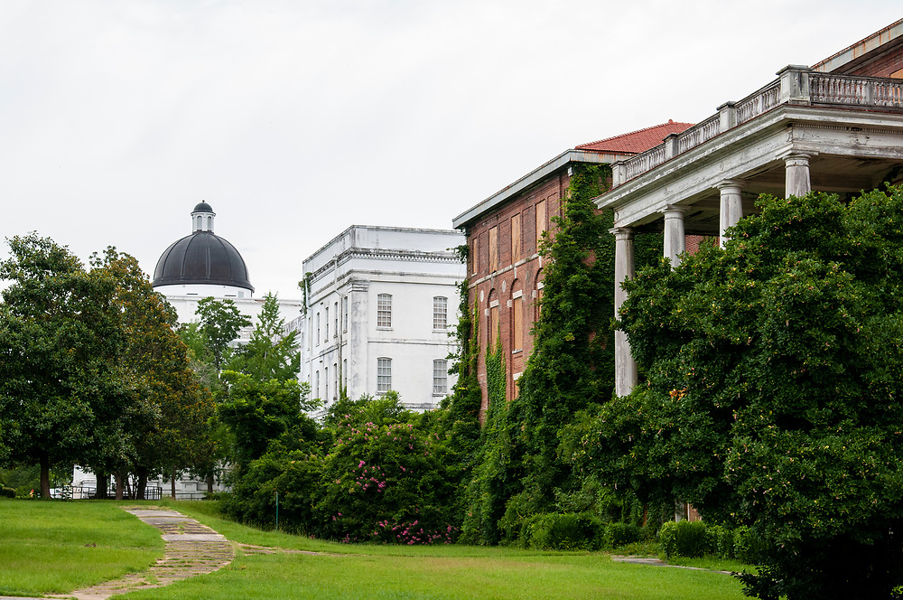 The Powell Building in the distance and abandoned Brantley Building at Central State Hospital in Milledgeville, Georgia on Sunday, July 18, 2021. Copyright 2021 Jason Barnette