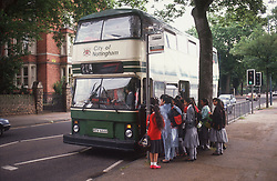 Group of school children waiting at bus stop before boarding bus,