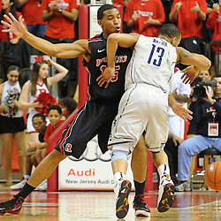 Connecticut Huskies guard Shabazz Napier (13) draws Rutgers Scarlet Knights guard/forward Derrick Randall (15) into a blocking foul during Rutgers' 67-60 upset victory over #8 UConn in NCAA Big East Basketball action at the Louis Brown Athletic Center in Piscataway, N.J. on Jan 7, 2012.
