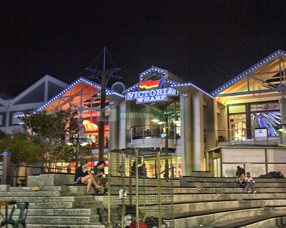 March 16, 2011 - Cape Town, Western Cape, South Africa - After dark visitors rest on the steps of the brightly illuminated Victoria Wharf Shopping Centre on the Victoria & Alfred Waterfront. In the historic heart of Cape Town harbor it is the most-visited tourist destination of South Africa. Set against a backdrop of sea and mountain views, it offers a variety of shopping and entertainment options. (Credit Image: © Arnold Drapkin/ZUMAPRESS.com)