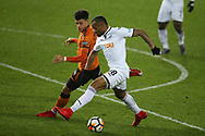 Jordan Ayew of Swansea city looks to go past Morgan Gibbs-White of Wolverhampton Wanderers. The Emirates FA Cup, 3rd round replay match, Swansea city v Wolverhampton Wanderers at the Liberty Stadium in Swansea, South Wales on Wednesday 17th January 2018.<br /> pic by  Andrew Orchard, Andrew Orchard sports photography.