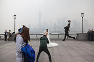 China, Shanghai. shooting chinese wedding on the Bund promenade, man jumping on a ball